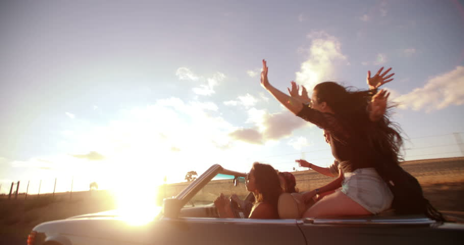 Rear view of a teenager girl enjoyng a road trip on a convertible car with friends on summer sunset