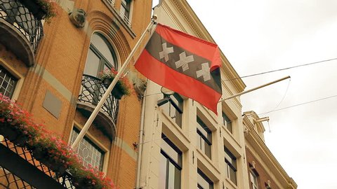 An Amsterdam flag is fluttering in the wind at the old building. Red flag with a black bar and white crosses.