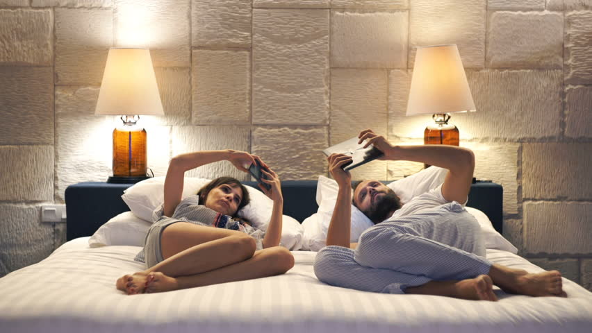 Young couple with smartphone and tablet lying on bed late at night at home