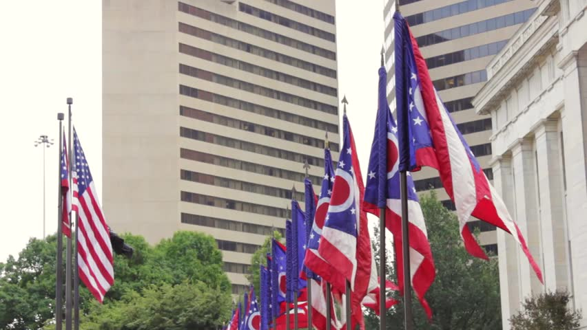 Ohio flags flying outside of Ohio Statehouse. USA flag in the background.