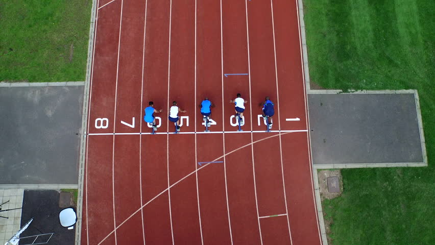4K Aerial view of track athletes at running track, competing in a race