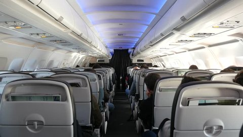 Jet airplanes interior view with unrecognizable people seated.