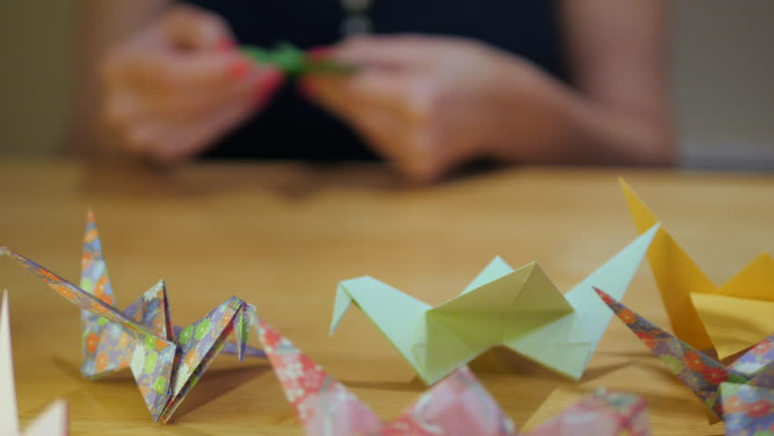cinema craft panning shot of girl makes paper crane origami from coloured paper