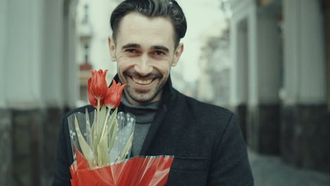 Happy smiling forty years old caucasian man with baguette and flower bouquet standing on the street. City buildings as background. RAW video rcord.