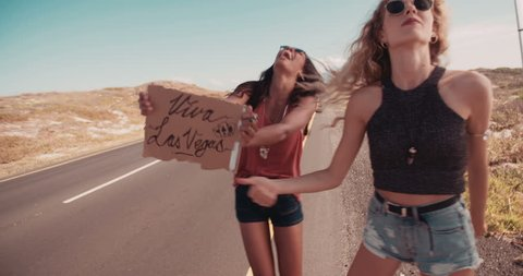 Two friends on a road trip; Blonde caucasian hipster girl and african american boho woman hitchhiking on roadside of highway with thumb out and holding cardboard sign viva Las Vegas