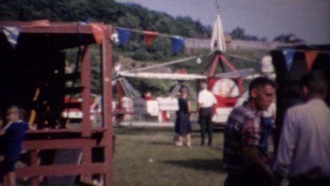 MONTICELLO, NEW YORK 1961: Carnival fair amusement ride park crowds enjoying summer.