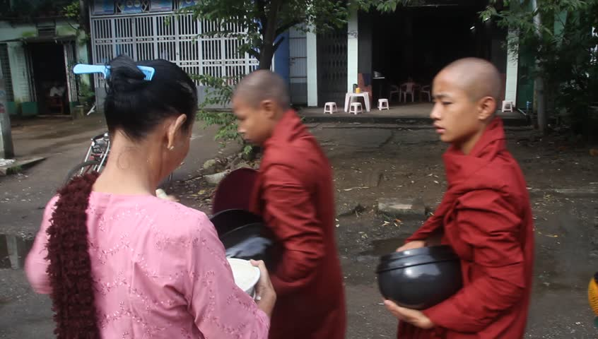YANGON, MYANMAR - 18 AUGUST 2011 - Buddhist monks receive food from local women circa August 18, 2011, Yangon, Myanmar.