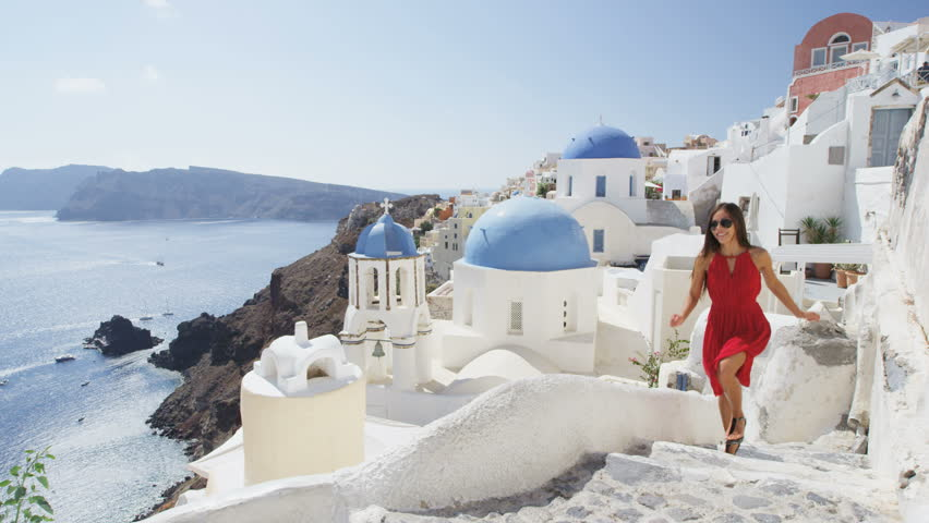 Happy woman in red dress climbing stairs on Santorini. Young female is on summer vacation in Santorini. She is visiting famous tourist attraction the blue domed church in Oia. RED EPIC.
