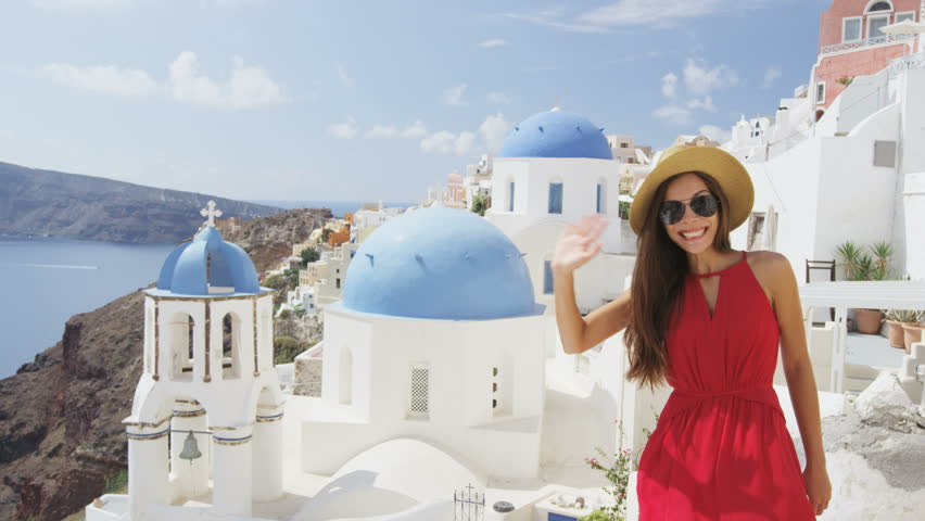 Excited young woman waving hello at village Oia, Santorini, Greece, Europe. Young tourist is visiting famous landmark tourist destinations wearing sunhat, sunglasses and red dress. SLOW MOTION. | Shutterstock HD Video #15325087
