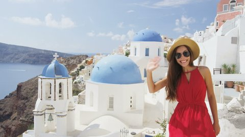 Excited young woman waving hello at village Oia, Santorini, Greece, Europe. Young tourist is visiting famous landmark tourist destinations wearing sunhat, sunglasses and red dress. SLOW MOTION.