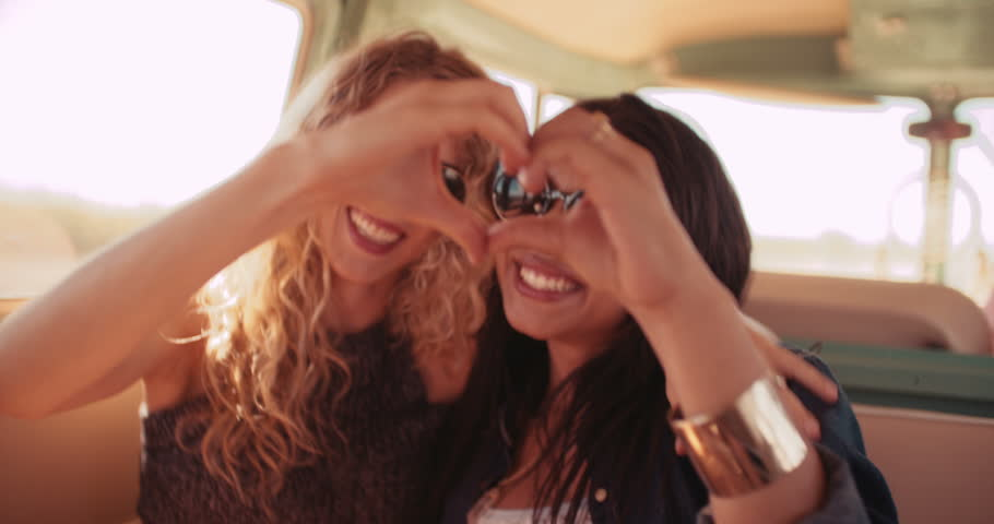 Best girl friends posing for photo on road trip both women making a hand heart in retro van.