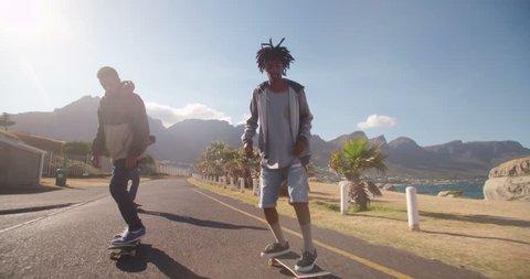 Multi-Ethnic group of skater friends skateboarding down road at seaside together during sunset