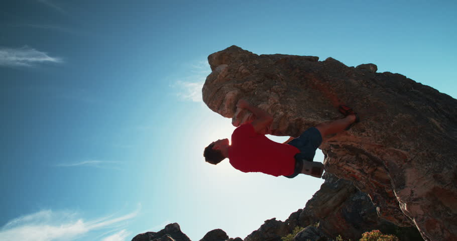 Low angle of strong rock climbing man hanging free on rock with sunflare against blue sky. | Shutterstock HD Video #15363097