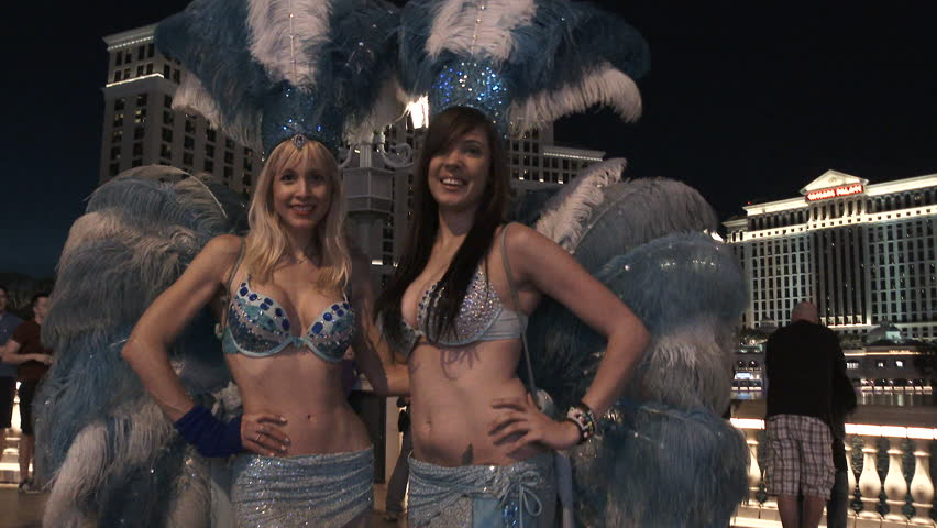 LAS VEGAS, NEVADA - CIRCA 2016: Two showgirls out front of the Bellagio Hotel and Casino at night welcoming you to Las Vegas, Nevada and the strip.