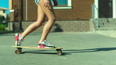 Slow motion shot of a beautiful style girl in skateboard in the city street
