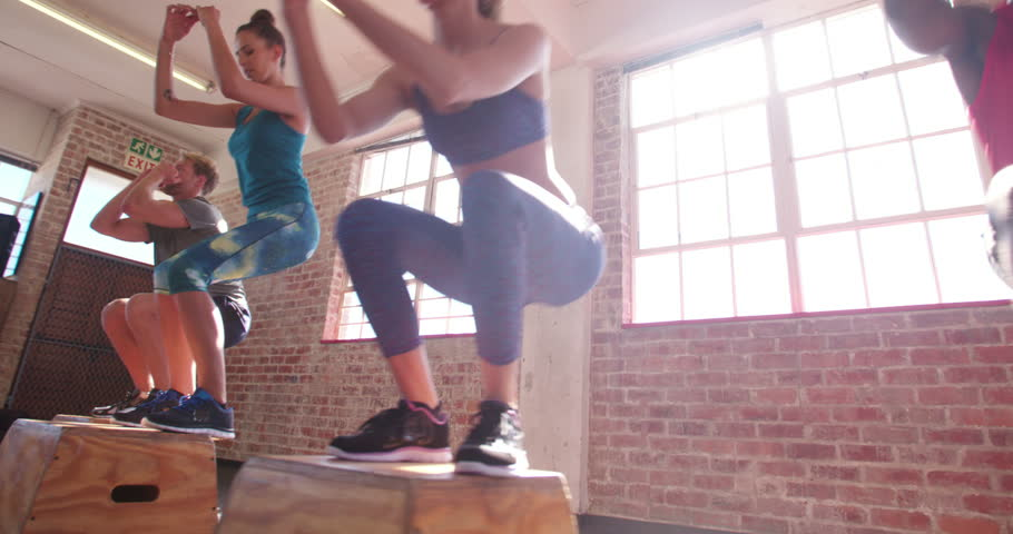 Multi-ethnic group of friends jumping onto wooden boxes in a crossfit training #15390187