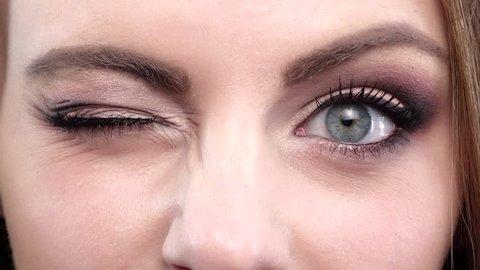 Woman winking. Blue eyes. Closeup