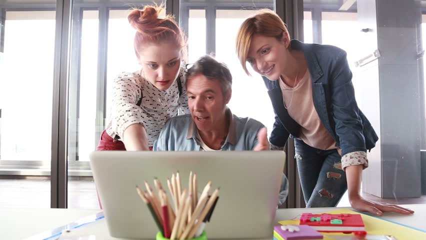 Middle age creative director looking at laptop with his team and discussing plans | Shutterstock HD Video #15414007