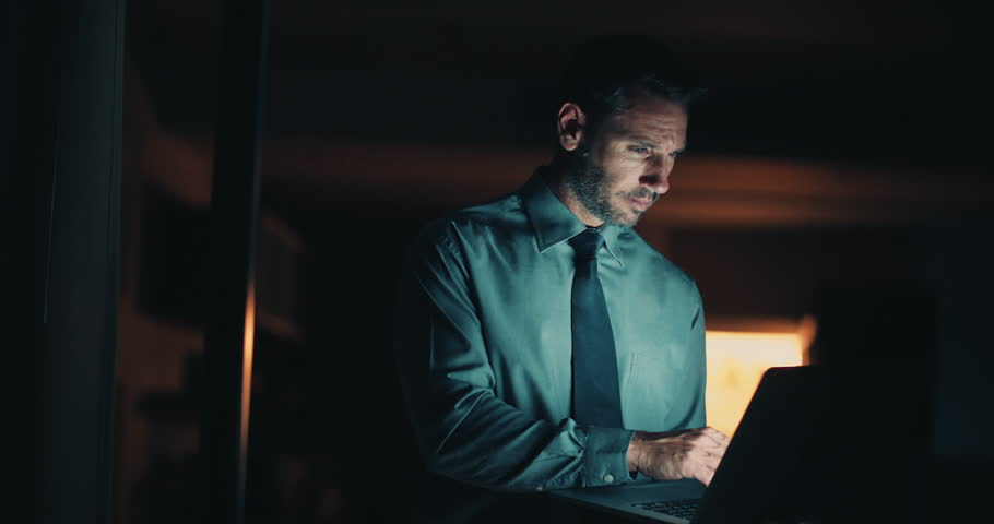 Serious man in blue shirt and blue tie working on laptop at night time in office | Shutterstock HD Video #15427750