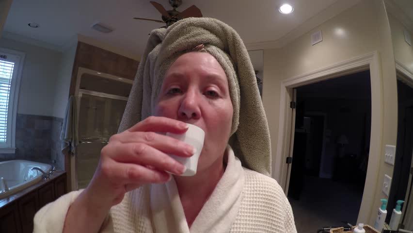 Mature woman wearing bathrobe in bathroom using mouthwash.