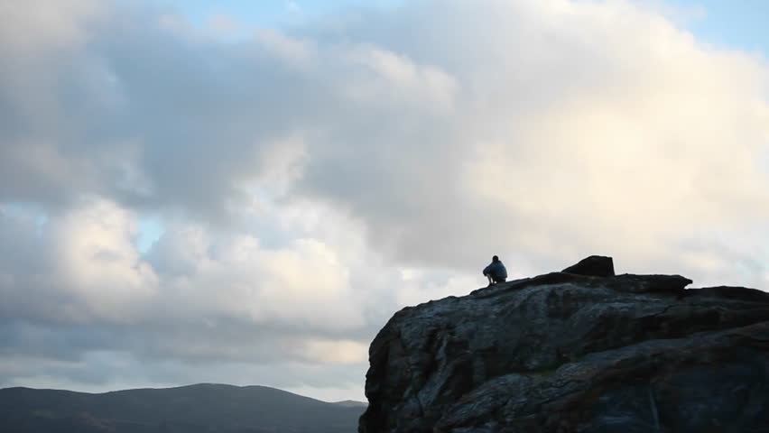 A person sits at the top of a rocky mountain.