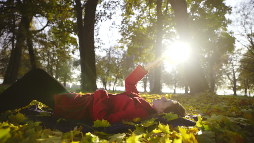 Woman lying on leaves while playing with leaf 4K. Low angle view of attractive woman in red coat laying on ground in forest, playing with leaf and sun shines from behind a tree.