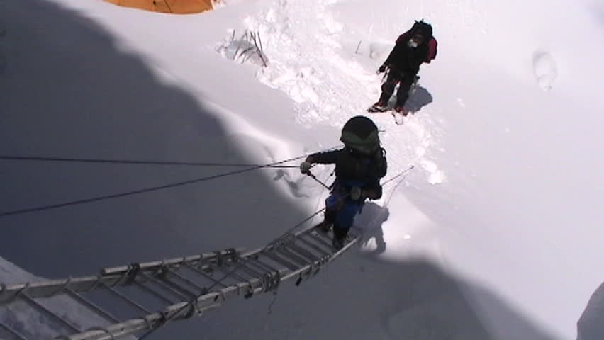 Climber climbs up ladder circa 2005 in Tibet.