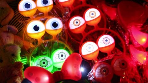 Medium close up of numerous blinking glowing eyeballs beeping and strobing at night. These are colorful blinking toys and novelty items being sold at night by a sidewalk vendor in Asia