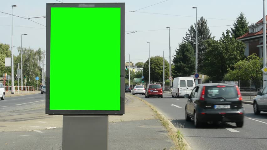 CZECH REPUBLIC, PRAGUE - JULY 7, 2015: billboard by the busy road in the suburb - green screen - car pass