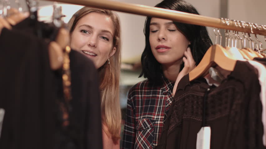 Young Adult Women Looking At Clothes In Shop