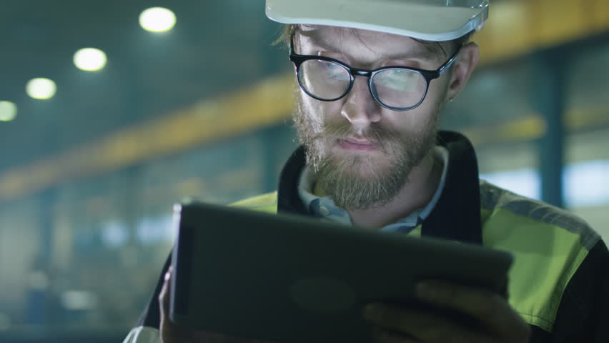 Engineer in hardhat is using a tablet computer in a heavy industry factory. Shot on RED Cinema Camera.