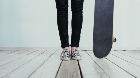 Teen girl standing with a a skateboard. 4K cinemagraph - motion photo seamless loop