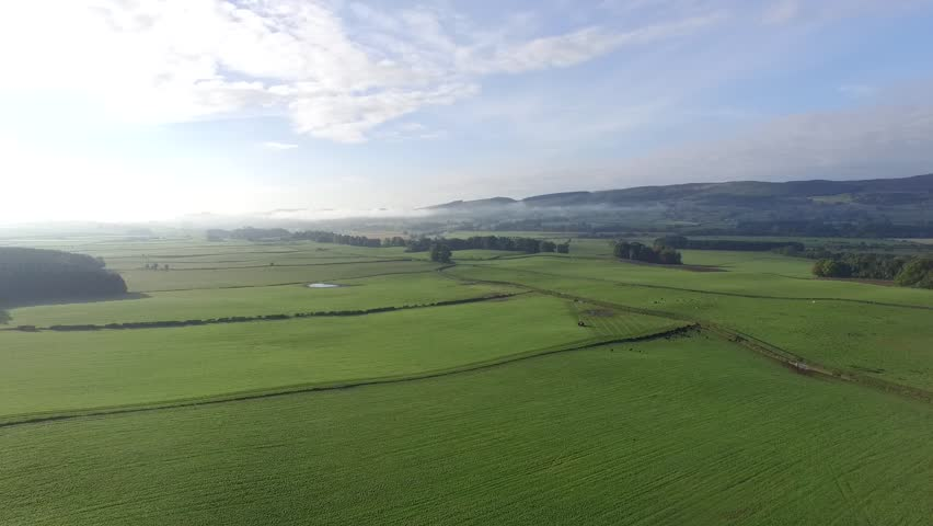 Aerial British farmland with clouds, blue sky and some morning mist and tractor in the distance