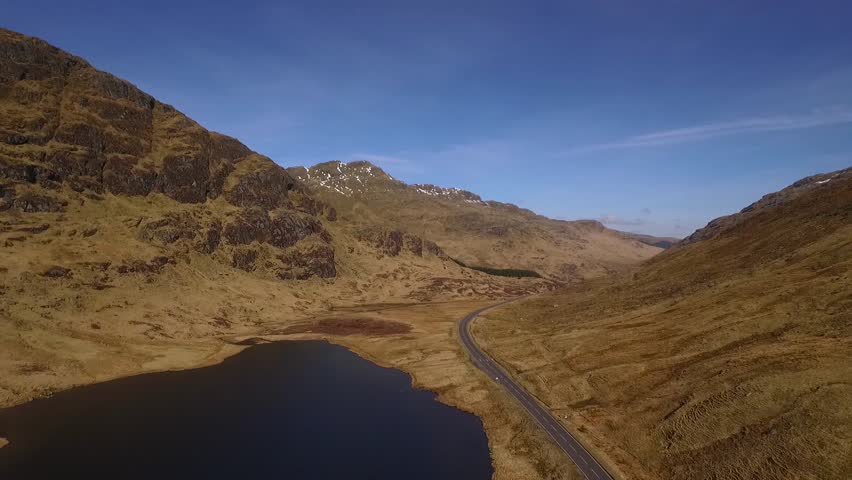 Aerial shot of road next to a loch in the Scottish highlands on a spring day