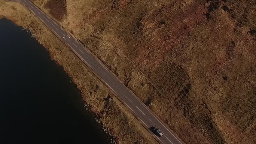 Aerial birds eye view of 1976 Landrover on Scottish country road next to a loch