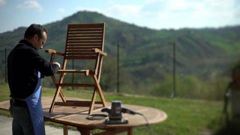 Backlit shot of handsome carpenter restoring a wooden chair with sandpaper. Garden furniture.