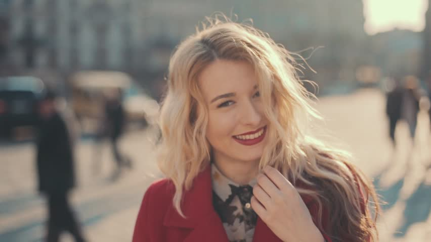 Attractive young woman with red lips in the city turning to camera and smiles, steady cam shot, slow motion