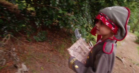 Boy dressed up as little pirate is excited to find the gold coins in treasure chest and is hunting through park after treasure with his map.