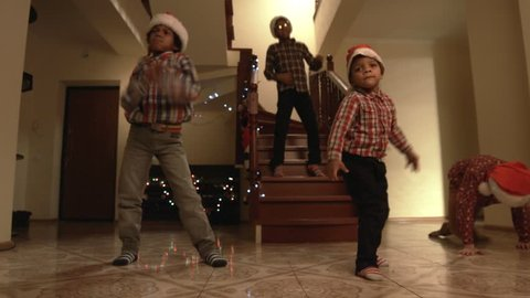 Kids in Santa hats dancing. Children dance freely on Christmas. Good way to express feelings. Time for a holiday dance.