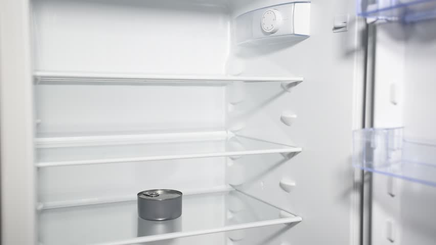 Fridge door opening and closing with one can inside. Diet and hunger concept. Nothing to eat in an empty refrigerator.