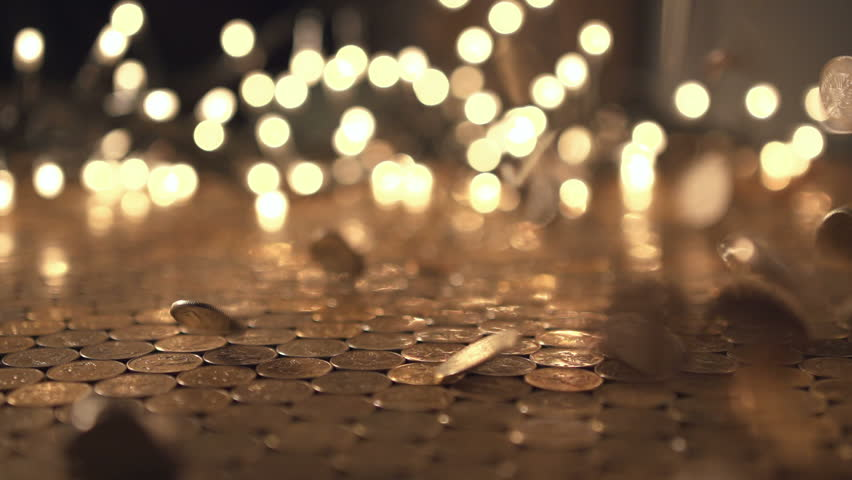 Pile of coins falling on the yellow table. Economic and financial crisis. Salary fall and pension increase, heap or bunch funds for buy for people. Close up of capital indoors. Studio slow motion