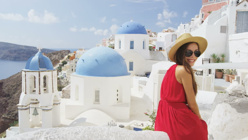 Tourist woman looking at view of beautiful village of Oia with blue domes on church. Young female model wearing sunglasses sunhat and red dress looking at camera enjoying travel vacation in Europe. | Shutterstock HD Video #15646837