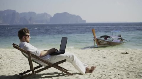 Dream work. Man works on the wonderful beach and enjoys his life. The happiest work. Freelance.