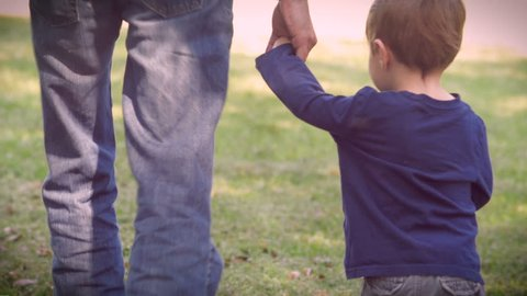 A father and son holding hands and walking away from the camera on green grass in a park or back yard somewhere when the little boy briefly looks up at the man while walking away.