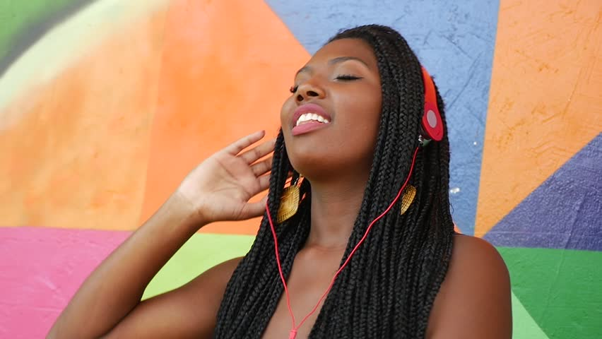 Brazilian afro woman listing to music on colorful background