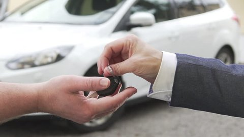 Car sale. A man selling a car to another man and handing over the key.