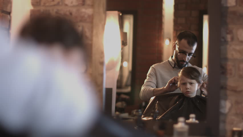 Hairdresser cutting hair of child in Barbershop #15758827