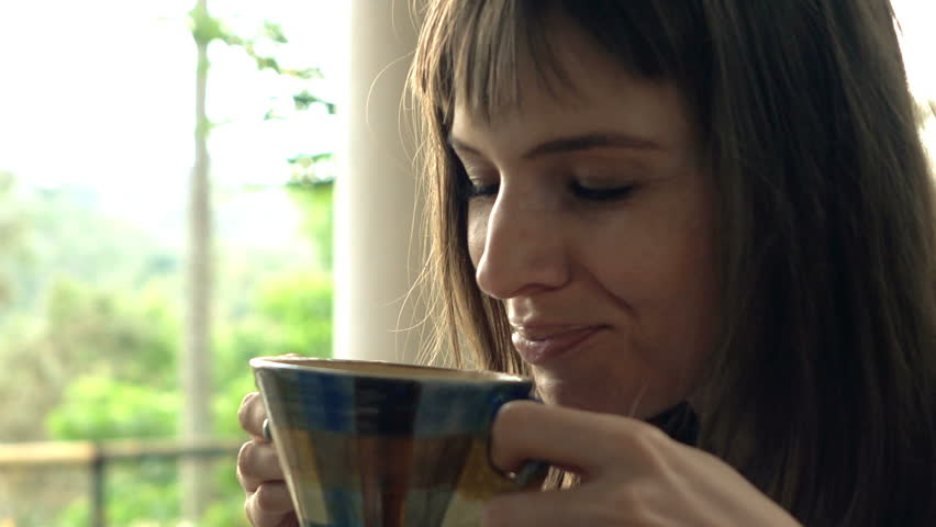 d443680f6ef Young, happy woman drinking coffee in garden, super slow motion 240fps