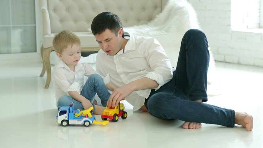 Dad And Young Son Playing Cars On The Floor. Happy European Family. On The