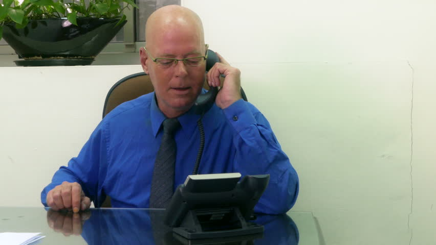 Businessman in office on phone taking notes, dolly in | Shutterstock HD Video #15775567